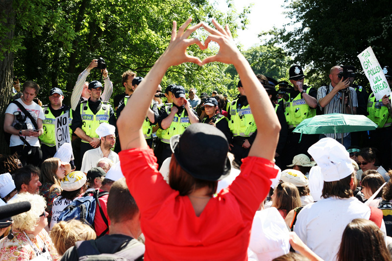 A protester makes a heart symbol in front of police forces outside the Rothamsted research centre in Hertfordshire, <br />where hundreds of activists gathered to demonstrate against open air trials of genetically modified wheat.<br />UNITED KINGDOM, Harpenden | 2012